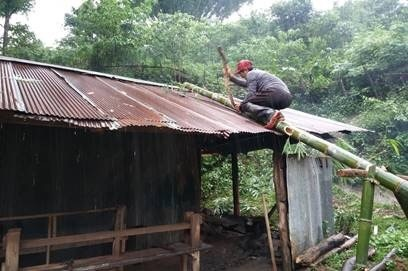 This is the kitchen and dining room. The storm tore a hole in the roof, so our teacher Pongsak is repairing it. No one in the village has a ladder, but you can always build one in an hour or so from a few stalks of bamboo.
